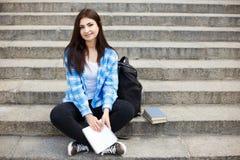 Giovane donna dello studente che si siede sulle scale della città con un libro nell'ha Fotografia Stock