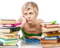 Giovane donna dello studente con i lotti dei libri che studia per gli esami Immagini Stock