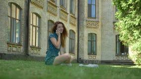 Giovane donna dello zenzero che parla sul telefono e che si siede sull'erba in parco con costruzione nel fondo, bello giorno sole stock footage