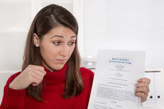 Giovane donna deludente che fissa al contratto di affari in tedesco Immagine Stock