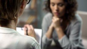 Giovane donna depressa che parla con psicologo di signora durante la sessione, salute mentale immagini stock libere da diritti