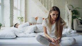 Giovane donna depressa che si siede a letto e che grida mentre il suo boylfriend che si trova a letto a casa fotografia stock