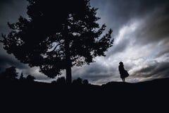 Giovane donna depressa che si siede sotto l'albero fotografia stock libera da diritti