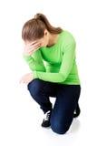 Giovane donna depressa integrale che si accovaccia Immagini Stock