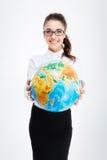 Giovane donna di affari affascinante felice vi che dà un globo della terra Immagine Stock
