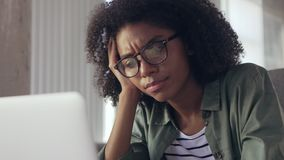 Giovane donna di affari africana di noia che lavora al computer portatile video d archivio