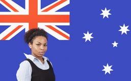 Giovane donna di affari afroamericana che sorride sopra la bandiera australiana fotografia stock