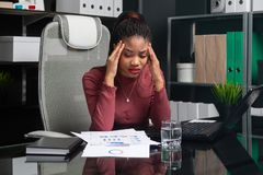 Giovane donna di affari afroamericana premurosa che si tiene per mano dietro la sua testa e che lavora con i documenti allo scrit fotografie stock libere da diritti