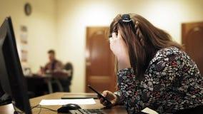 Giovane donna di affari al suo scrittorio ed al suo collega alla parte posteriore, sia spillante sul telefono all'ufficio archivi video