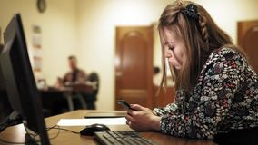 Giovane donna di affari al suo scrittorio ed al suo collega alla parte posteriore, sia spillante sul telefono all'ufficio video d archivio
