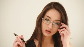 Giovane donna di affari allegra nella penna di tenuta di vetro in mani ed esaminare macchina fotografica su fondo bianco stock footage
