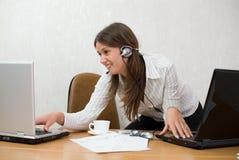 Giovane donna di affari allo scrittorio con due computer portatili Fotografia Stock