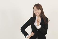 Giovane donna di affari asiatica attraente con una penna Fotografie Stock Libere da Diritti