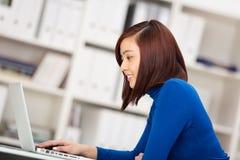 Giovane donna di affari asiatica che per mezzo di un computer portatile Fotografia Stock Libera da Diritti