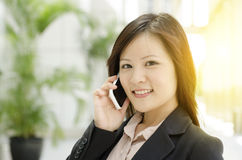 Giovane donna di affari asiatica che rivolge al telefono fotografia stock