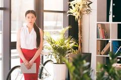 Giovane donna di affari asiatica che tiene compressa digitale e che esamina macchina fotografica fotografia stock