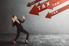 Giovane donna di affari asiatica colpita con la tassa sulla freccia che va giù Immagini Stock