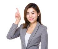 Giovane donna di affari asiatica con il dito su fotografia stock