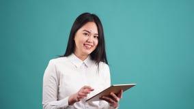 Giovane donna di affari asiatica Using Tablet Computer su fondo blu stock footage
