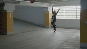 Giovane donna di affari attraente che indossa salto convenzionale del vestito e dancing divertente in un parcheggio sotterraneo s video d archivio