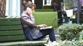 Giovane donna di affari attraente che per mezzo del computer portatile su una rottura all'aperto video d archivio