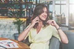 Giovane donna di affari attraente che si siede da solo alla tavola in caffè e che chiama dal telefono cellulare fotografie stock libere da diritti