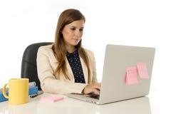 Giovane donna di affari attraente del ritratto corporativo alla sedia dell'ufficio che lavora allo scrittorio del computer portat Immagine Stock