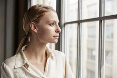 Giovane donna di affari bionda che guarda dalla finestra immagine stock