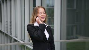 Giovane donna di affari bionda graziosa con lo smartphone video d archivio