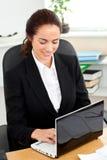 Giovane donna di affari carismatica che per mezzo del suo computer portatile Fotografie Stock Libere da Diritti