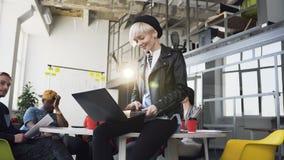 Giovane donna di affari caucasica che lavora al computer portatile mentre il suo cowoker che discute le idee di affari video d archivio