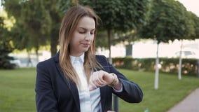 Giovane donna di affari che aspetta e che esamina il suo orologio, all'aperto archivi video