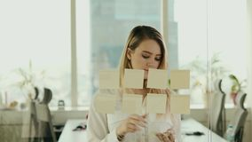 Giovane donna di affari che attacca le note appiccicose sul vetro all'ufficio video d archivio