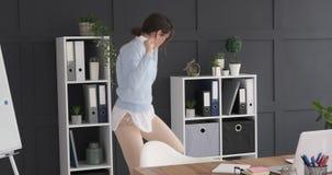 Giovane donna di affari che balla nell'ufficio stock footage