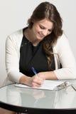 Giovane donna di affari che compila un'applicazione Fotografie Stock Libere da Diritti