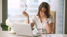 Giovane donna di affari che decolla i vetri stanchi di lavorare al computer portatile archivi video
