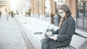 Giovane donna di affari che esamina lo schermo del computer portatile nella via Immagini Stock