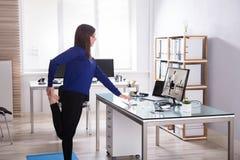 Giovane donna di affari che fa yoga fotografia stock