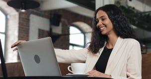 Giovane donna di affari che finisce il suo lavoro sul computer portatile ed e rilassato all'ufficio moderno archivi video