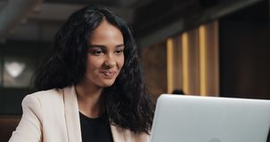 Giovane donna di affari che ha video chiamata con il suo capo sul computer portatile all'ufficio moderno Bella donna che parla co video d archivio