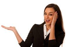 Giovane donna di affari che indica lo spazio della copia, mostrante un prodotto Fotografia Stock