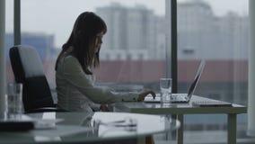 Giovane donna di affari che lavora ad un computer portatile in ufficio moderno archivi video