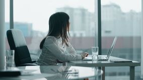 Giovane donna di affari che lavora ad un computer portatile in ufficio moderno che sorride e prende una rottura archivi video