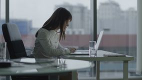 Giovane donna di affari che lavora ad un computer portatile in ufficio moderno ha messo a fuoco e serio video d archivio