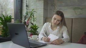 Giovane donna di affari che lavora al computer portatile in caffè video d archivio