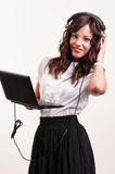 Giovane donna di affari che lavora al computer portatile e che ascolta la musica sulla h Immagine Stock Libera da Diritti