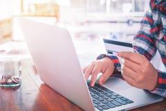 Giovane donna di affari che lavora al suo computer portatile e che usando la carta di credito Fotografia Stock
