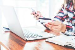 Giovane donna di affari che lavora al suo computer portatile e che usando la carta di credito che si siede alla tavola di legno Fotografia Stock Libera da Diritti