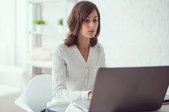 Giovane donna di affari che lavora allo scrittorio che scrive su un computer portatile in ufficio Fotografia Stock