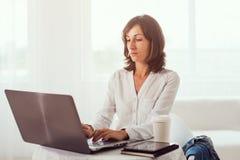 Giovane donna di affari che lavora allo scrittorio che scrive sulla a Immagine Stock